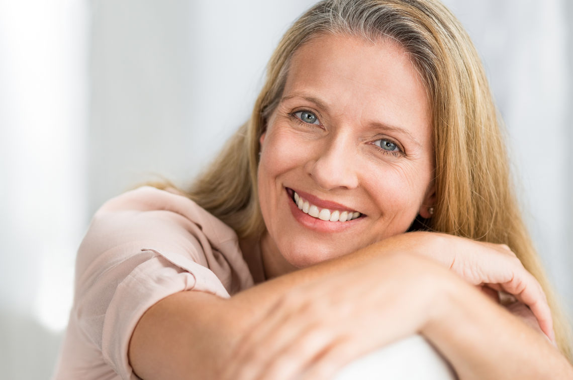 smiling mature woman on couch jehuqvg